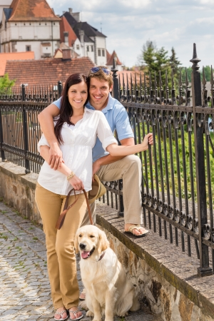 Young couple with dog posing at historical town sunny day photo