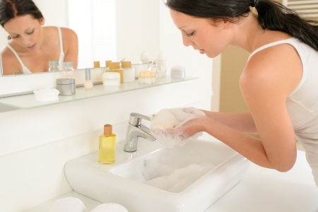 lavamanos: Mujer joven en el ba�o lav�ndose las manos con jab�n en barra
