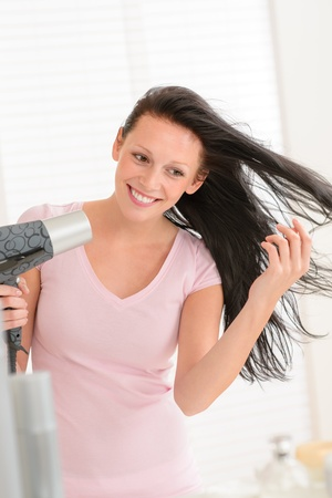Smiling brunette woman blow-drying long hair in bathroom Stock Photo - 14658336