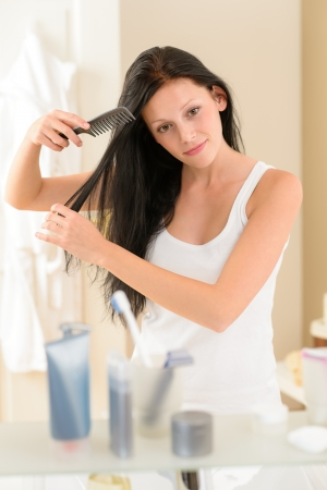 comb: Brunette woman brushing long hair in front of bathroom mirror Stock Photo