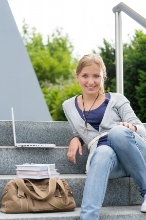 Happy student girl sitting on university steps laptop and books photo