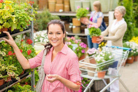 Young woman shopping flowers at garden centre green house photo