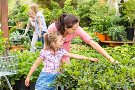 Mother and daughter choosing flowers at garden centre shop Stock Photo - 14735489