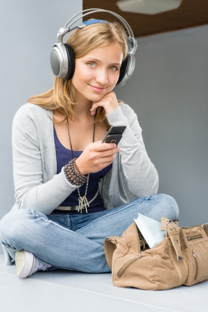 girl headphones: Young woman holding her mobile phone sitting wall outdoor