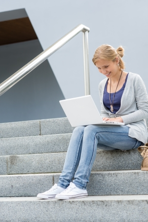 Student girl on stairs with laptop computer smiling outdoor Stock Photo - 14735617