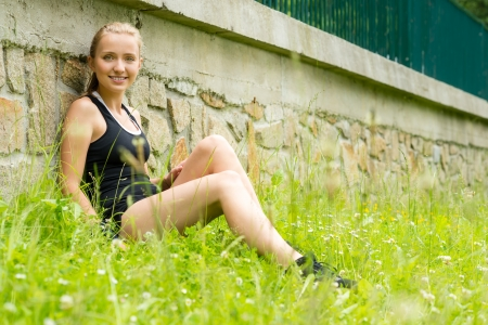 blithe: Young sportive woman relax in grass workout outdoors leisure Stock Photo
