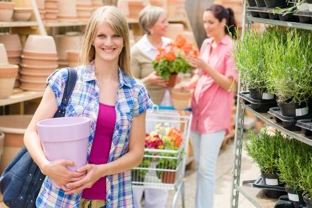 gamme de produit: Jeune blonde tenant pot de fleur dans le jardin de centre de commerce de d�tail Banque d'images