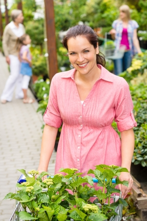 Smiling woman buy flowers at garden centre pushing shopping cart photo