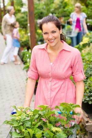 Smiling woman buy flowers at garden centre pushing shopping cart Stock Photo - 14823845
