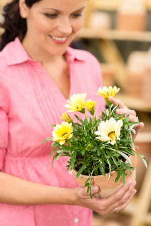 Portrait smiling woman hold yellow potted flowers in garden shop photo