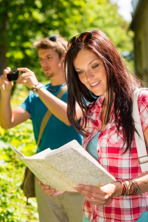 Young tourist couple travel holiday with map and photographing camera photo