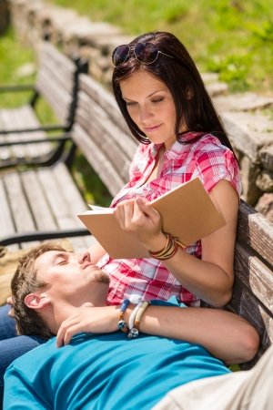 Young happy couple relax on park bench woman read book photo