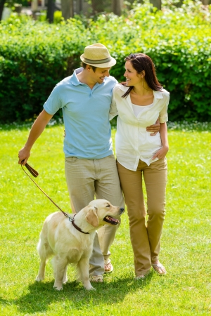 Happy couple walking golden retriever dog on park lawn smiling photo