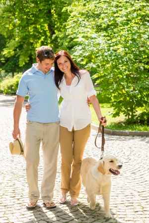 Couple in love walking Labrador dog in park sunny day photo