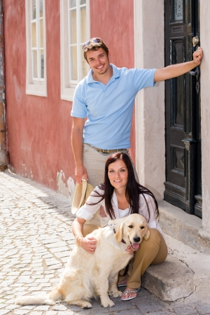 Young couple resting with dog on street stairs happy pet photo