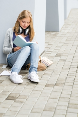 Teenage student girl study siting ground outside university building photo