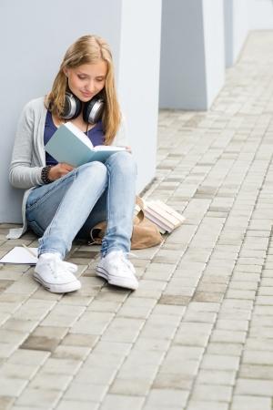 Teenage student girl study siting ground outside university building photo