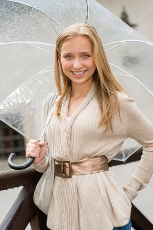 blithe: Mujer joven feliz en traje de lluvia con paraguas sonriendo ciudad Foto de archivo