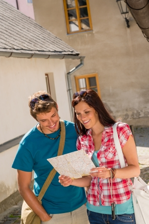 Happy couple looking at map in town travel vacation destination photo