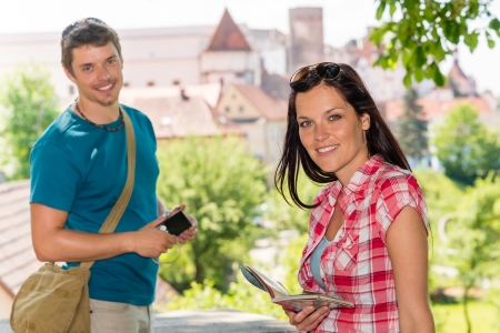 Young woman holding map man with camera happy smiling tourists photo
