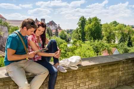 tourist destination: Young happy couple on vacation in city looking at map