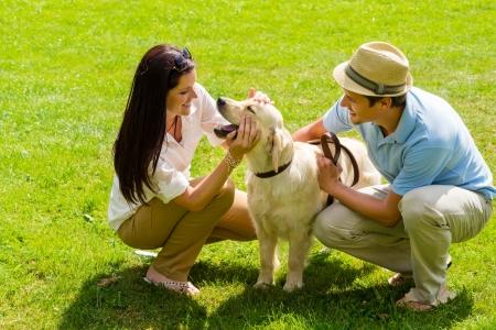 perro labrador: Feliz pareja joven que juega con el perro Labrador sonriente en el parque