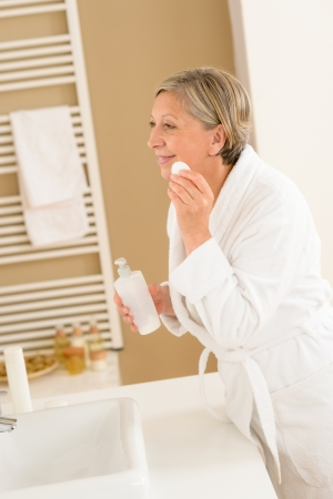 Mature woman in bathroom clean face make-up removal looking mirror Stock Photo - 14899955