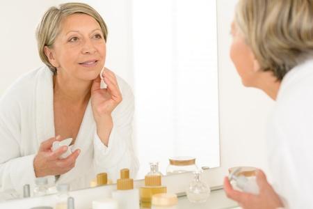 sch�ne frauen: H�bsche �ltere Frau im Badezimmer besah sich im Spiegel