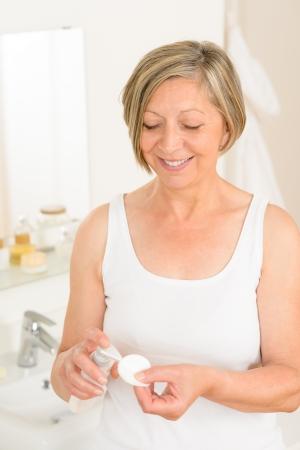 woman face cream: Senior woman in bathroom apply facial cream cotton pad