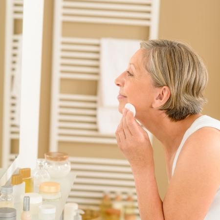 pulizia viso: Anziano, donna, faccia pulita con un batuffolo di cotone cercando specchio del bagno