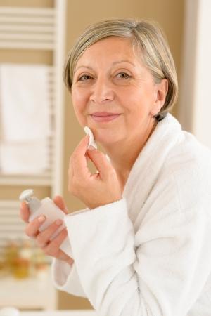 pulizia viso: Senior donna in bagno guardando la fotocamera pulizia crema viso