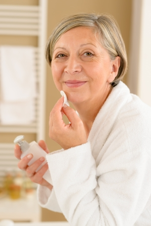 woman bathrobe: Senior woman in bathroom looking at camera cleaning facial cream