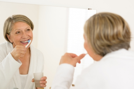 Mature woman brushing teeth with toothpaste looking in bathroom mirror photo