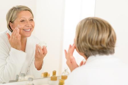 visage: La mujer mayor que mira en el espejo del ba�o y la aplicaci�n de anti-arrugas crema Foto de archivo
