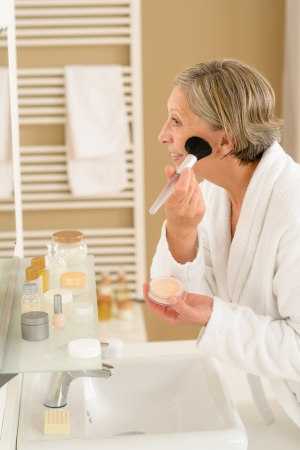 Senior woman apply make-up powder in front of bathroom mirror Stock Photo - 14899964