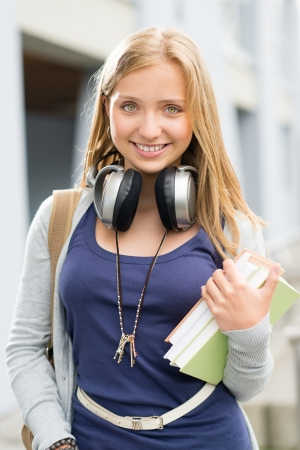 Young teenage student girl with books headphones smiling at camera photo