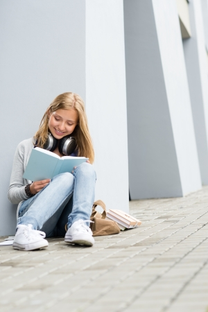 Smiling young study woman read book outdoor high-school building photo