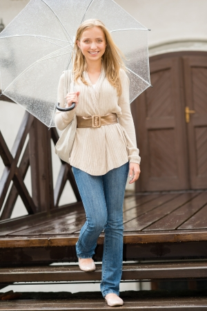 Woman stepping down the stairs with umbrella happy smiling rain photo