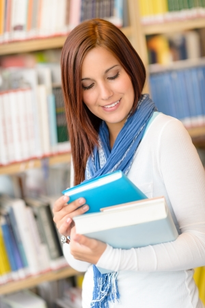 studious: Female high school student at library reading book