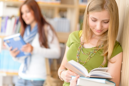Happy female blonde student at library read books high school photo