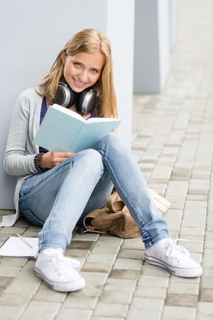 Smiling student girl reading book outside of school sitting ground photo