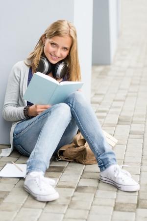 assis par terre: Student girl Sourire lecture du livre de l'ext�rieur du terrain de l'�cole assis