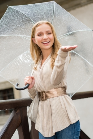 blithe: Young happy woman in rain with umbrella city look Stock Photo