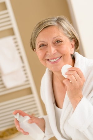 cotton pad: Senior woman clean face with cotton pad  looking at camera