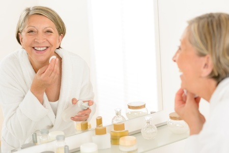 Senior woman smiling cleaning face make-up removal bathroom mirror reflection photo