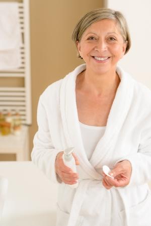 Senior woman wear bathrobe standing in bathroom with hygiene products photo