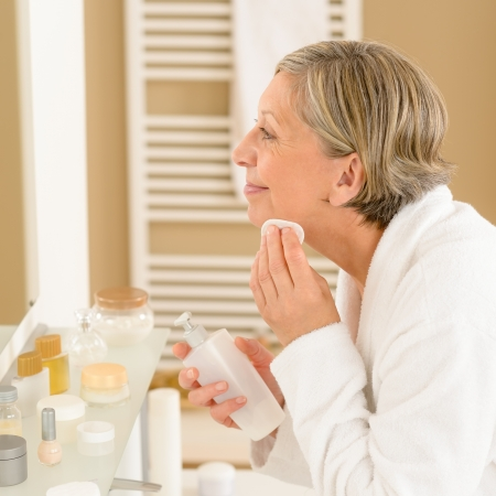 Senior woman in bathroom clean face make-up removal looking mirror photo
