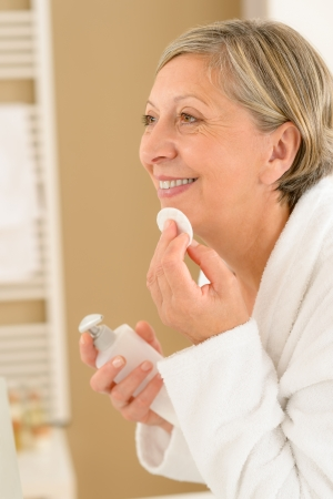Senior woman in bathroom clean face make-up removal smiling photo