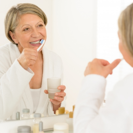 Senior woman brushing teeth looking at herself in bathroom mirror photo