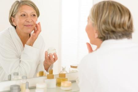 Senior woman looking in bathroom mirror applying anti-wrinkles face cream photo